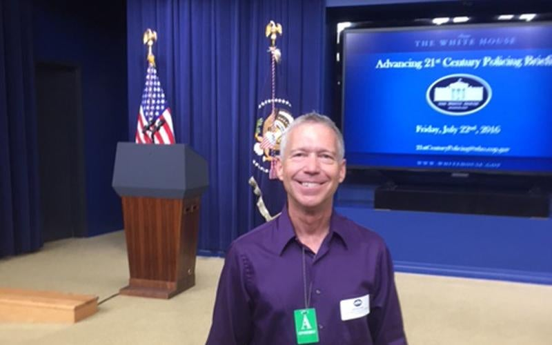 Chief John Edmundson in the White House briefing room with the presidential flag and podium behind him.